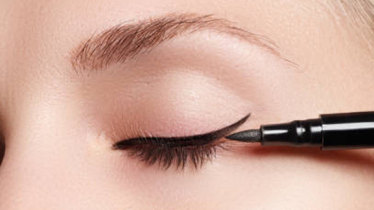 Beautiful model applying eyeliner close-up on eye